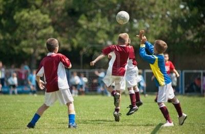 ragazzini-che-giocano-a-calcio-sul-campo-sportivo
